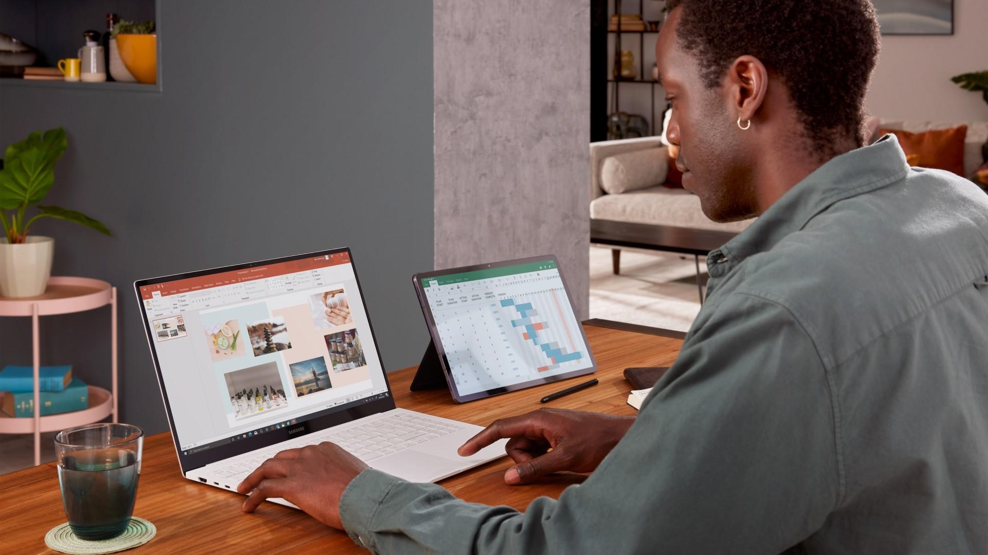 Hombre sentado en el escritorio con ordenador portátil y tableta para trabajar