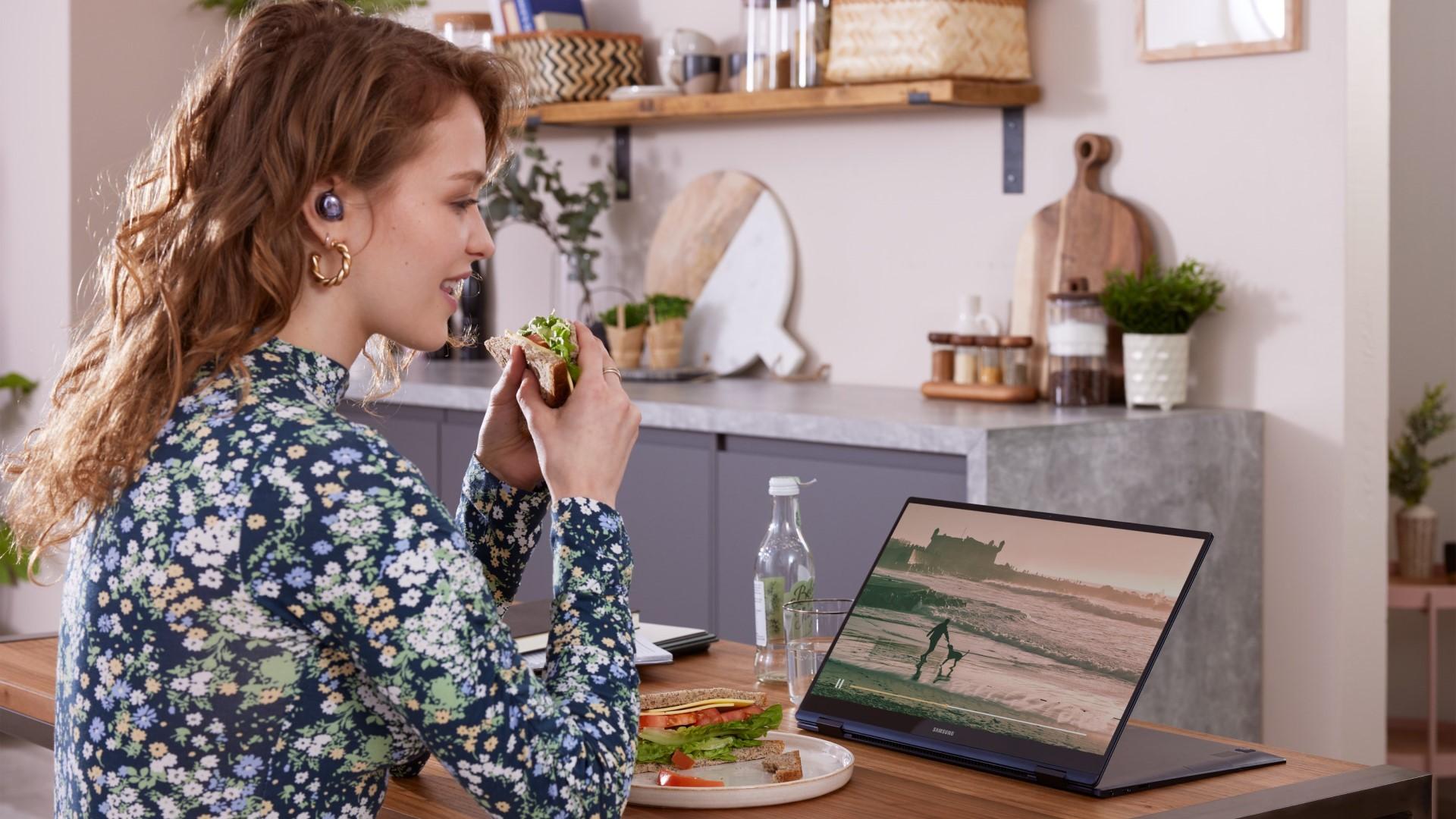 Mujer comiendo sándwich en la cocina viendo la película en el portátil