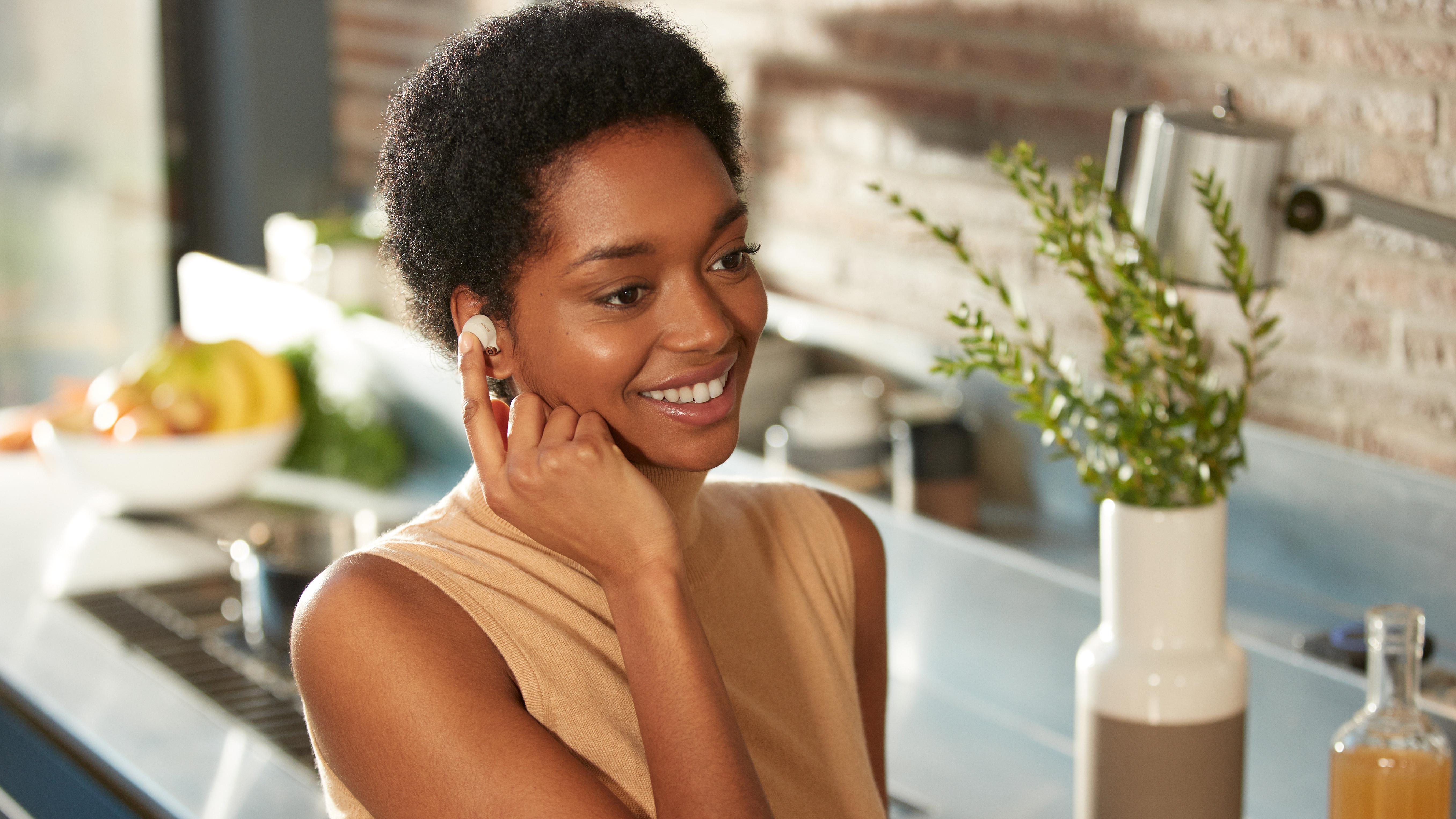 Una mujer presiona uno de los auriculares Sony WF-1000XM4