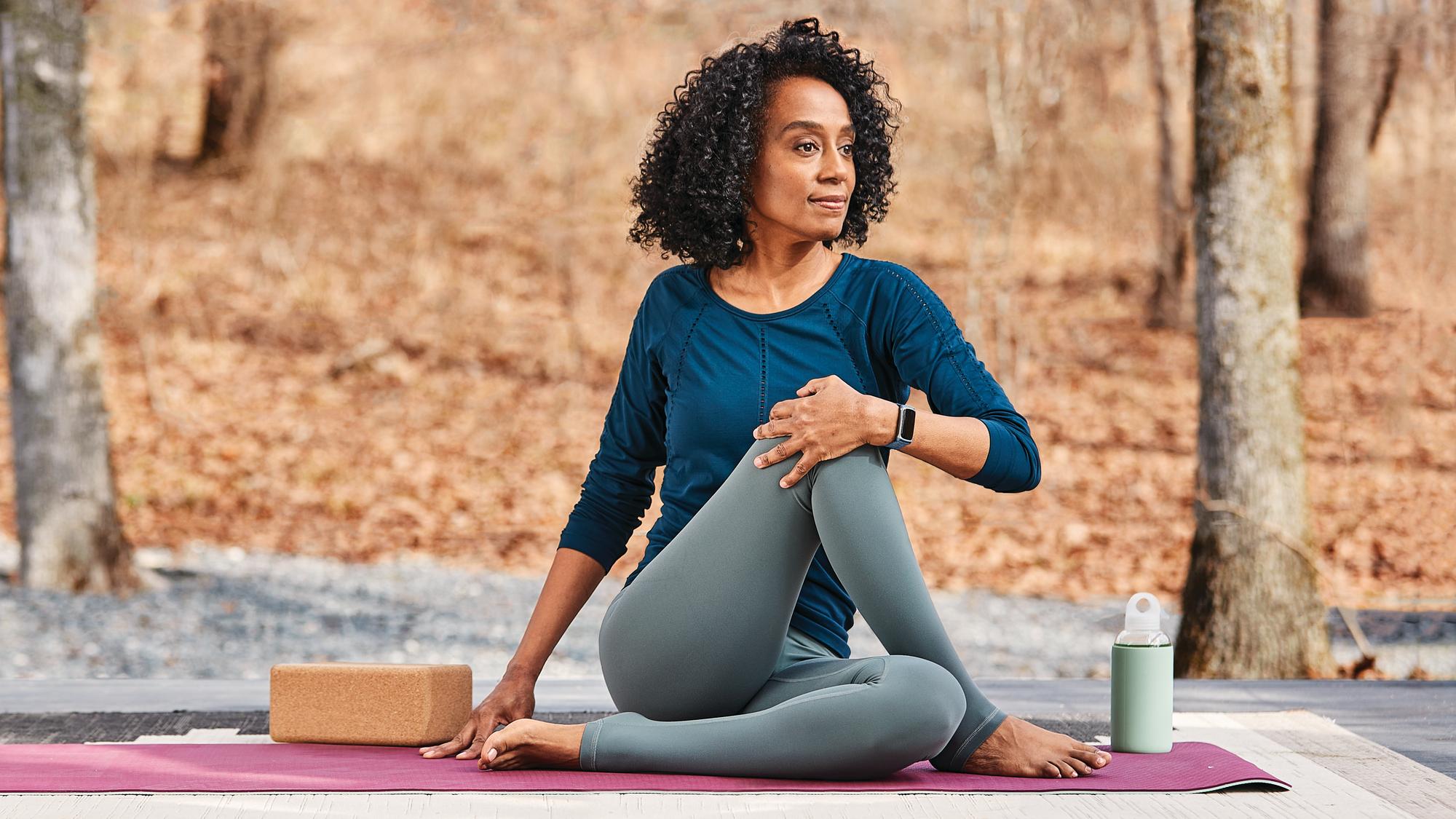 Mujer haciendo yoga vistiendo Fitbit Charge 5