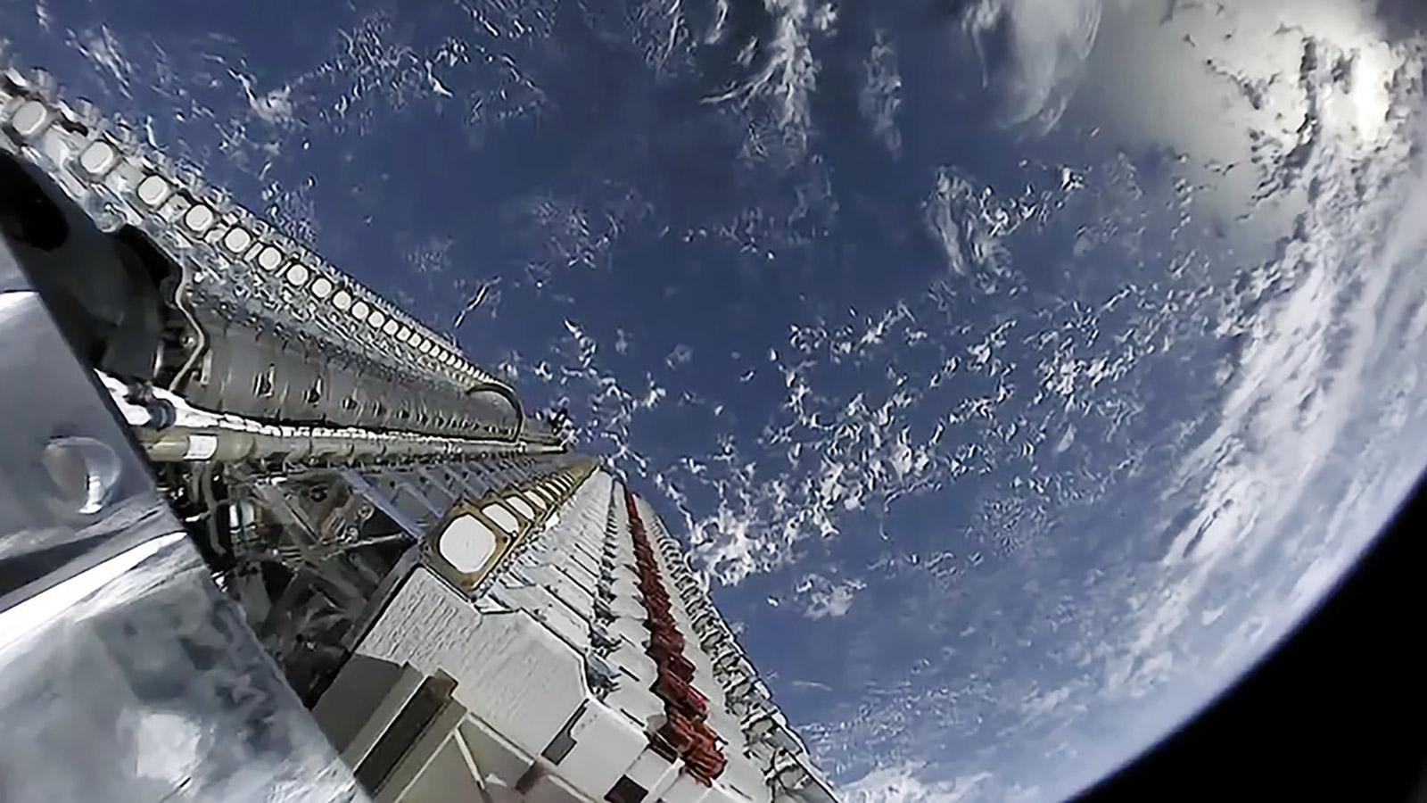 Los satélites SpaceX Starlink esperan para orbitar con la Tierra en segundo plano