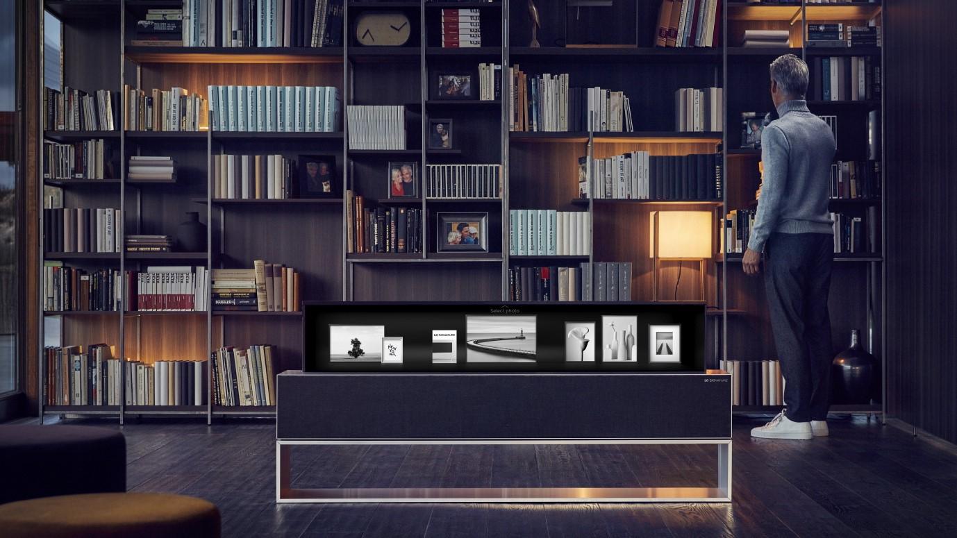 El televisor OLED se enrolla en posición enrollada, frente al estante