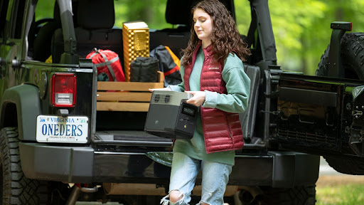 Una mujer con equipo de campamento saca una mini central eléctrica portátil DELTA de la parte trasera de un jeep.