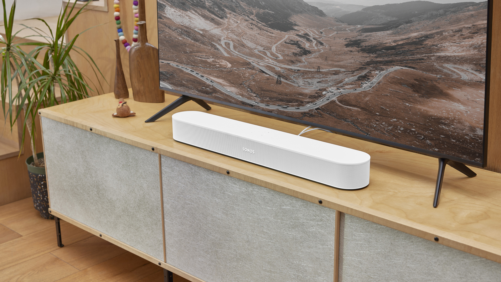 la barra de sonido sonos beam en blanco en un mueble de televisión