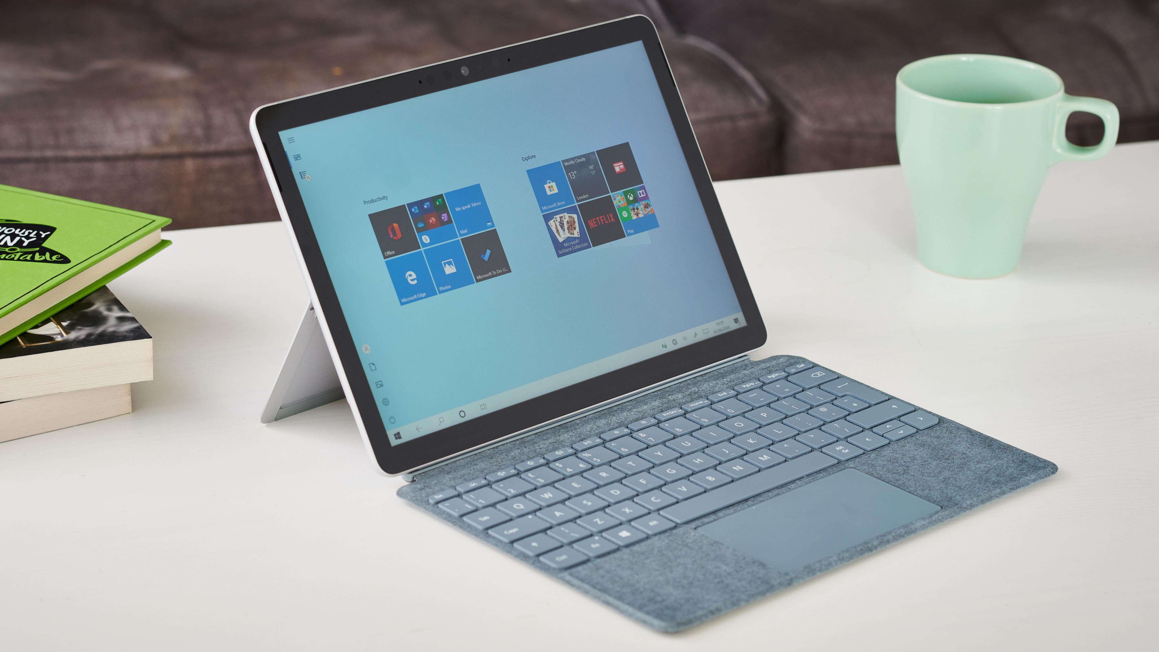 Microsoft Surface Go 2 en una mesa de café blanca junto a una pila de libros y una taza de café de menta